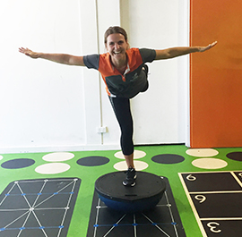 Woman balancing on one leg on an upside down BOSU ball